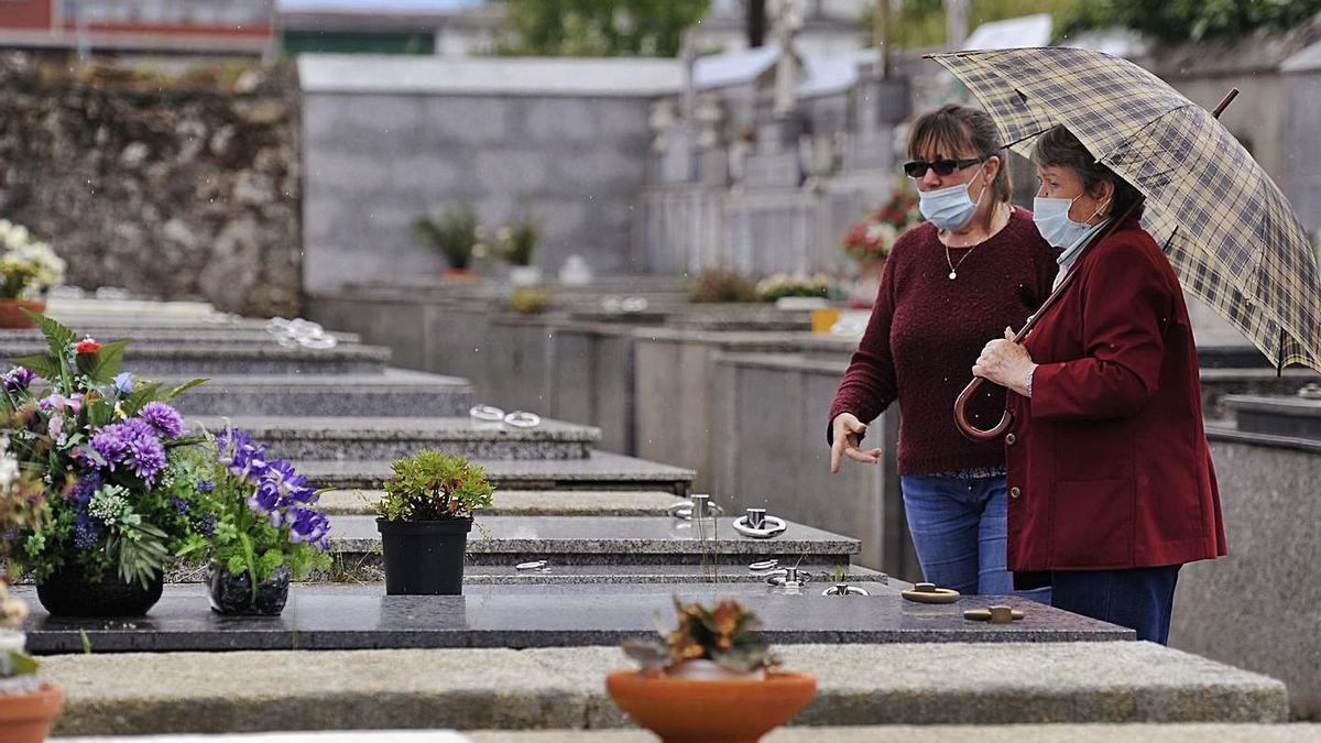 Dos mujeres, con mascarilla, en un cementerio gallego.  | // BERNABÉ / JAVIER LALÍN