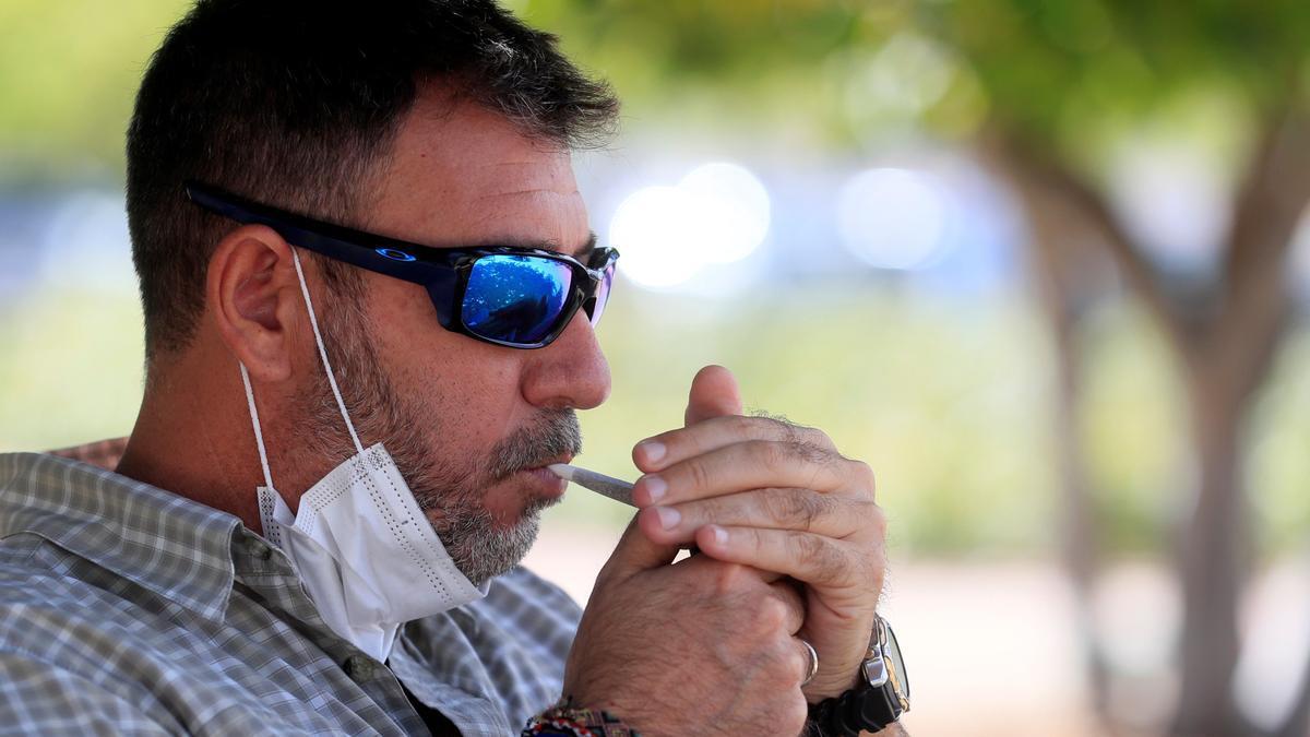 Un hombre se baja la mascarilla para encender un cigarro
