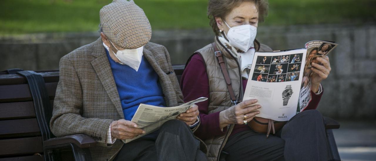Una pareja lee en un banco del Campo San Francisco, en Oviedo