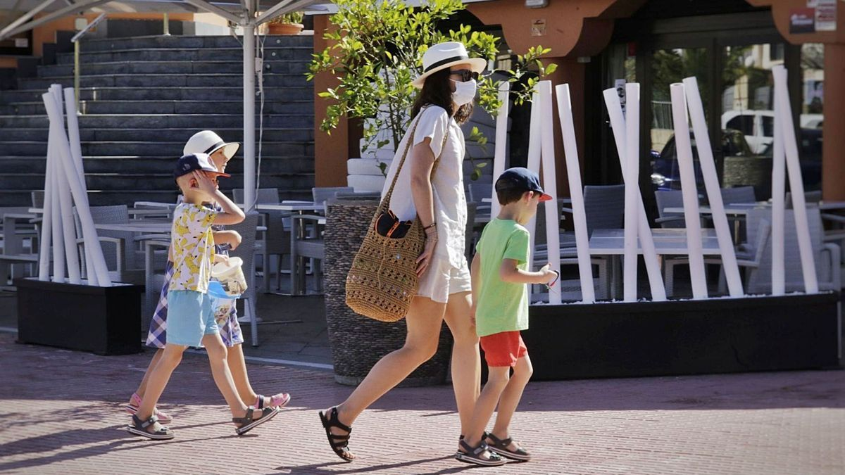 Una turista con sus hijos en Costa Adeje, sur de Tenerife.