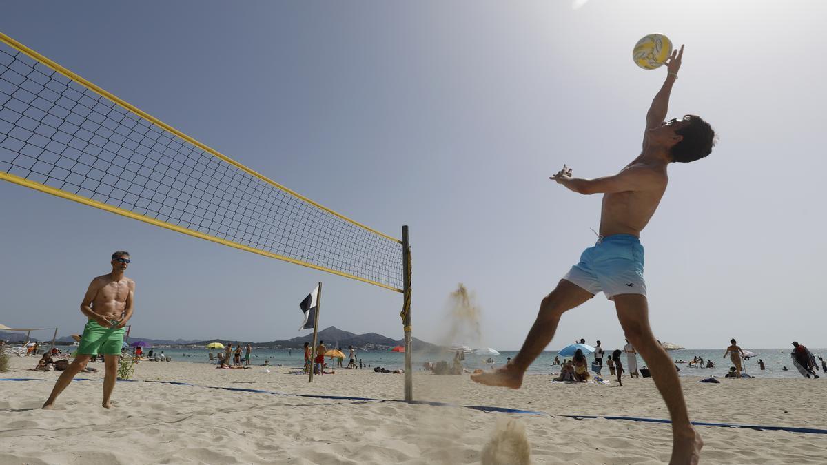 Deutsche Urlauber spielen Beachvolleyball an der Playa de Muro auf Mallorca.