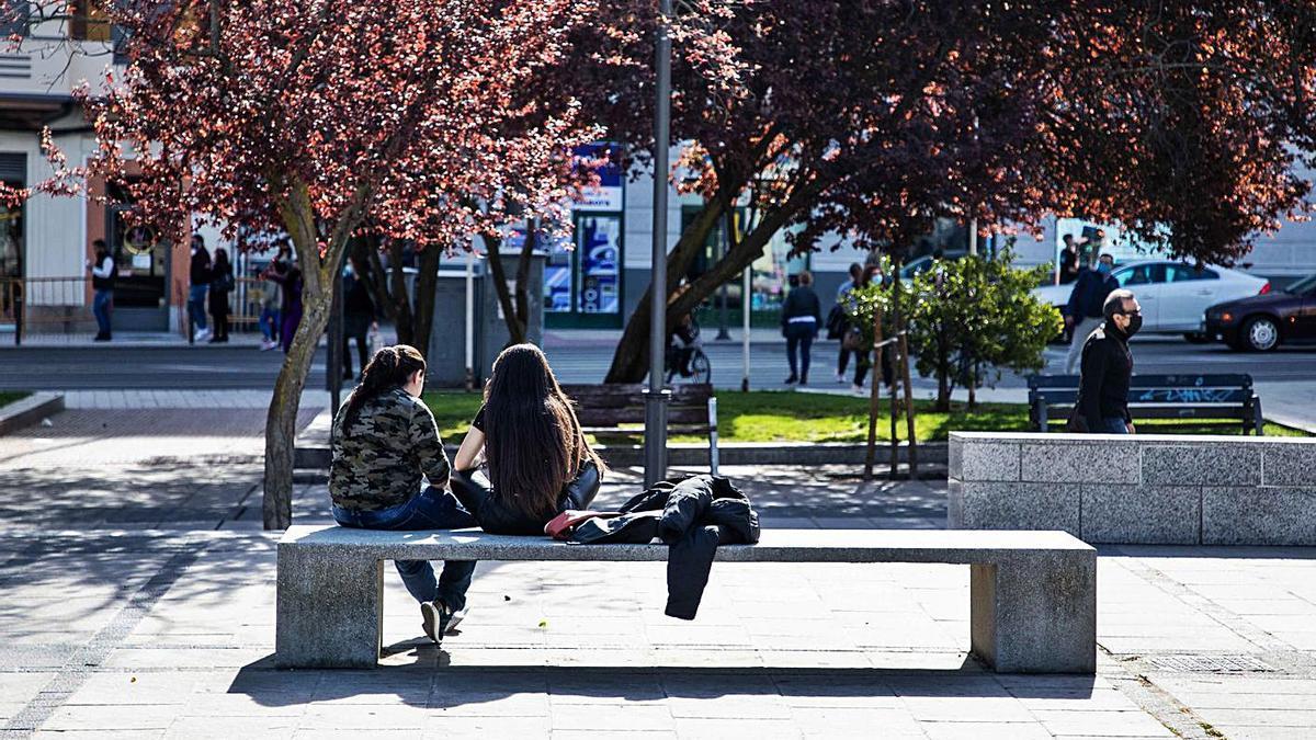 Dos jóvenes disfrutan de la temperatura primaveral que reina en Zamora.