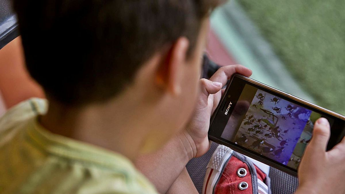 Un niño de corta edad jugando con un móvil en imagen de archivo.