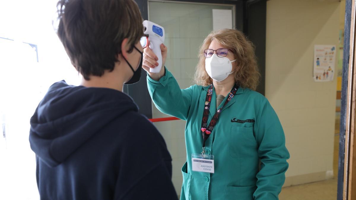 Una asistente covid toma la temperatura en un centro sanitario.
