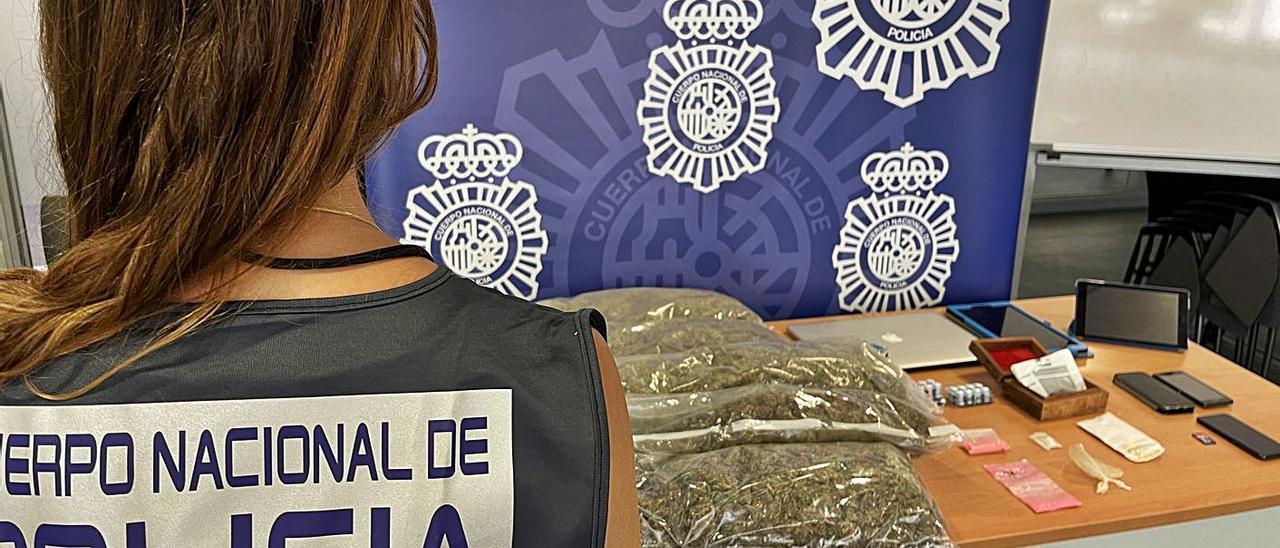 Una policía nacional junto a las drogas incautadas al detenido en Alicante.