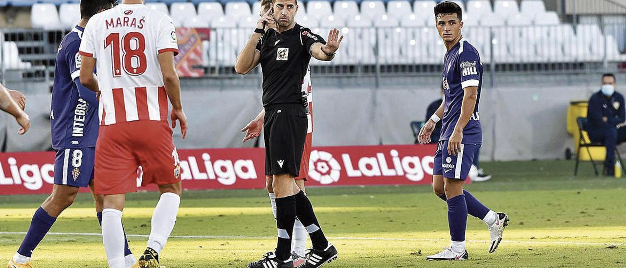 Ávalos Barrera consulta con el VAR. A la derecha, Aitor entre dos jugadores del Almería.
