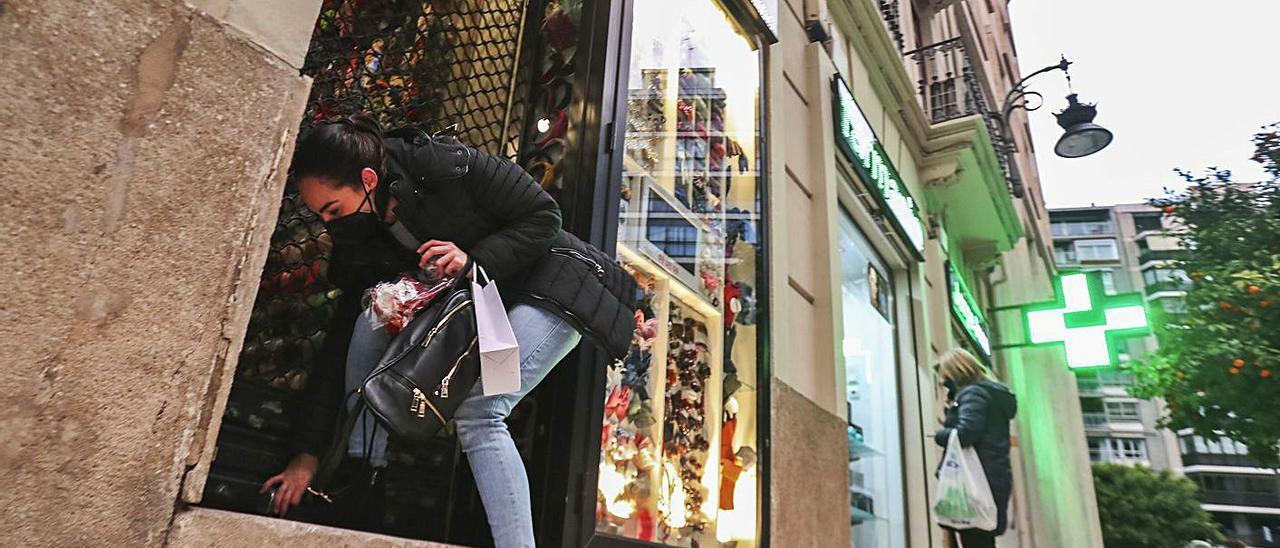 A la izquierda, una trabajadora cierra su comercio de la calle Jorge Juan de València. A la derecha, persianas bajadas pocos minutos después de las 18.00 horas. | F. CALABUIG