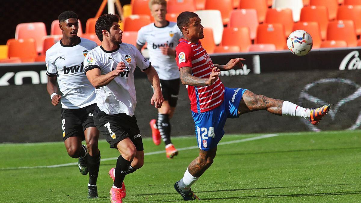 Robert Kenedy controla la pelota ante la presión de Gonçalo Guedes, en el último Valencia-Granada. | J.M. LÓPEZ