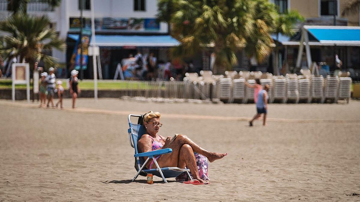 Una mujer toma el sol en la playa de Los Cristianos. | | ANDRÉS GUTIÉRREZ