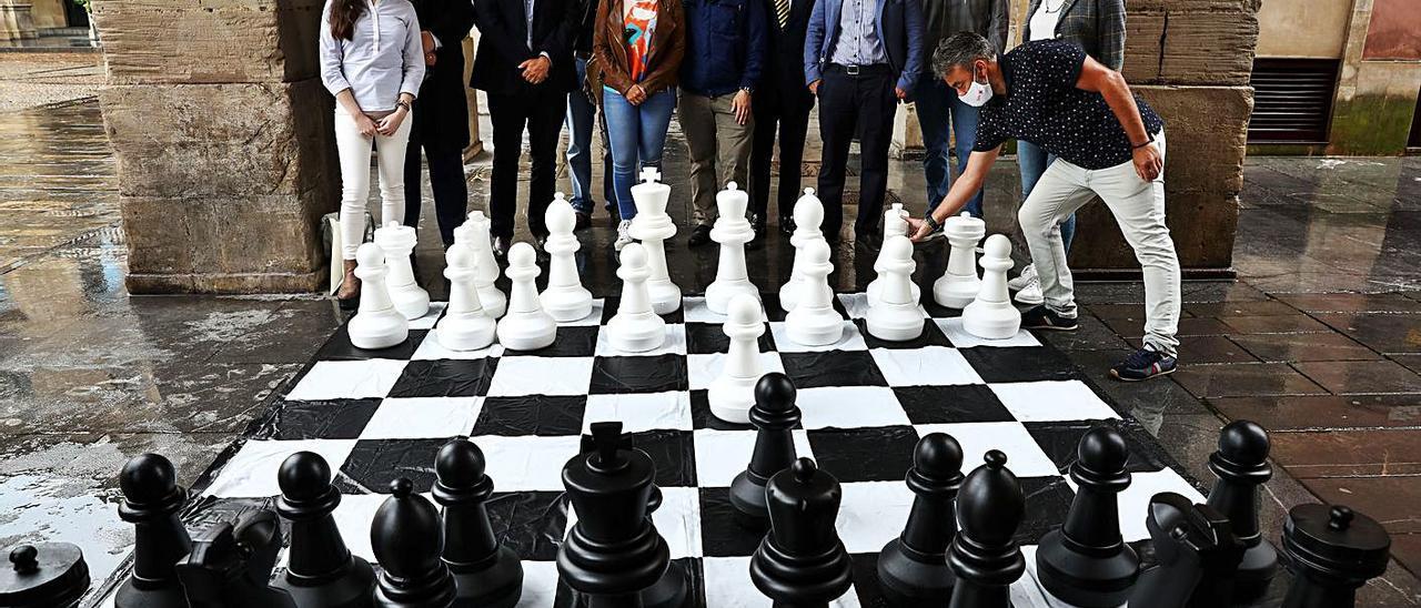 Asistentes a la presentación del campeonato ante un ajedrez gigante, ayer, en la Plaza Mayor de Gijón. | Juan Plaza