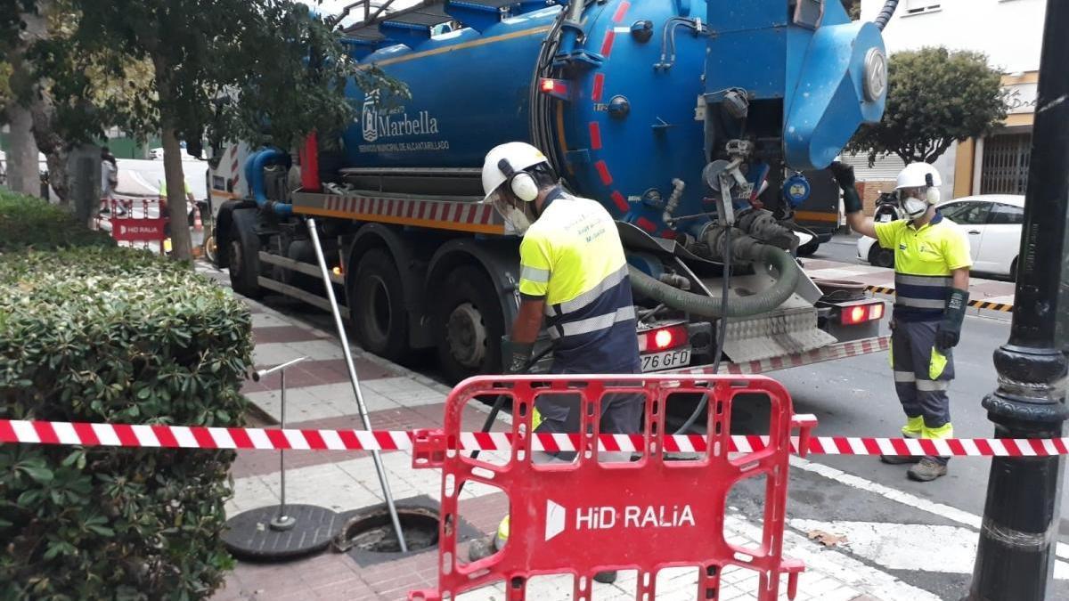 Dos operarios limpian una alcantarilla en una de las calles del municipio.