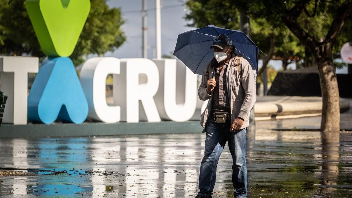 Un hombre camina frente a las letras corpóreas de Santa Cruz de Tenerife.