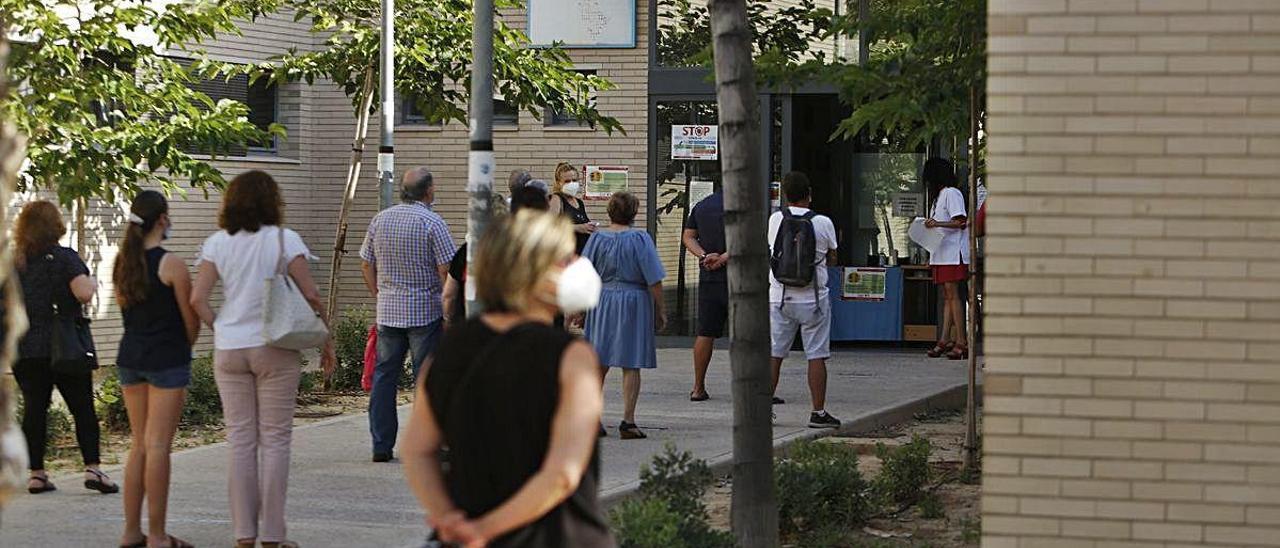 Usuarios del centro de salud Cabo Huertas, en Alicante, hacen cola hasta conseguir que les atiendan en el mostrador y a su vez les llame su médico otro día para citarles.