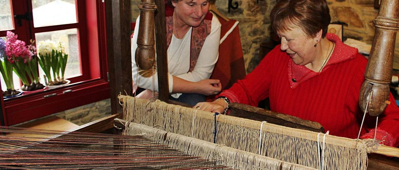 La artesana Pilar Quintana, en el centro de artesanía de Bres, trabajando en el telar, bajo la mirada de Inés Barcia, en una imagen de archivo.| Tania Cascudo