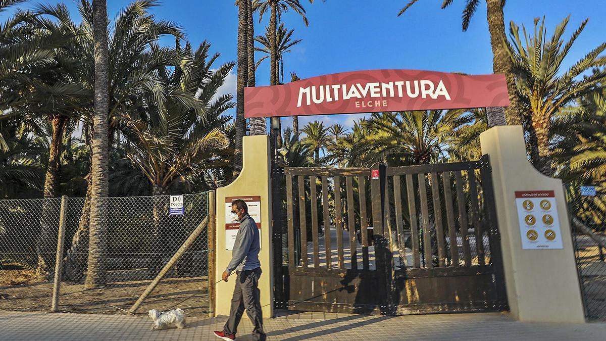 Un vecino de Travalón pasa delante de la entrada cerrada de Elche Multiaventura, ayer.