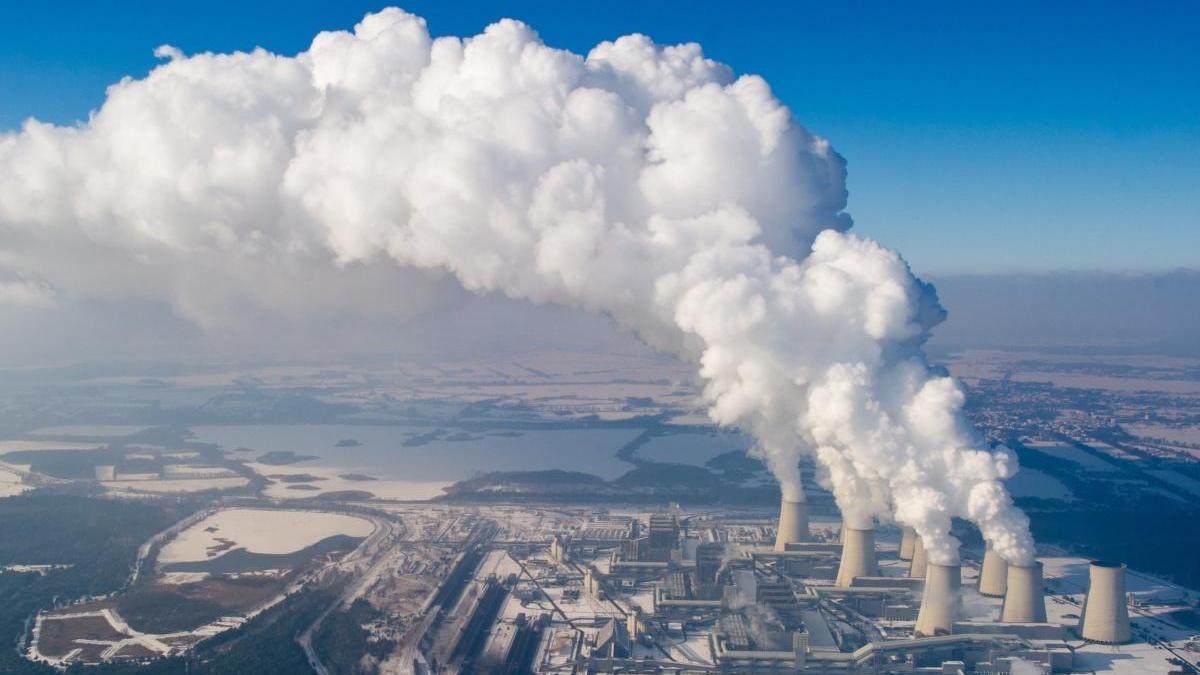 Varias columnas de vapor de agua emergen de una central eléctrica.
