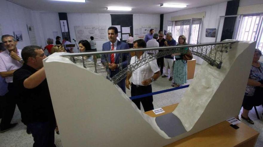 El delegado de la Junta observa la maqueta del Puente de Requejo que se expone en Bermillo.