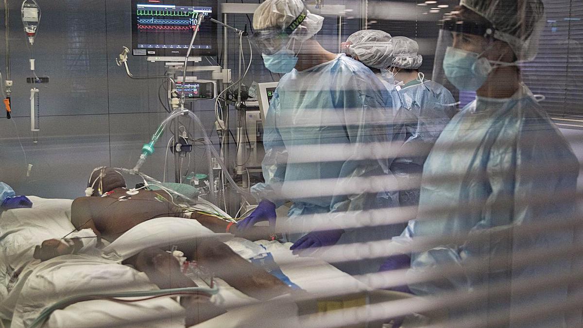 Professionals sanitaris atenen un pacient amb coronavirus a l'UCI de l'hospital Trueta. | DAVID APARICIO