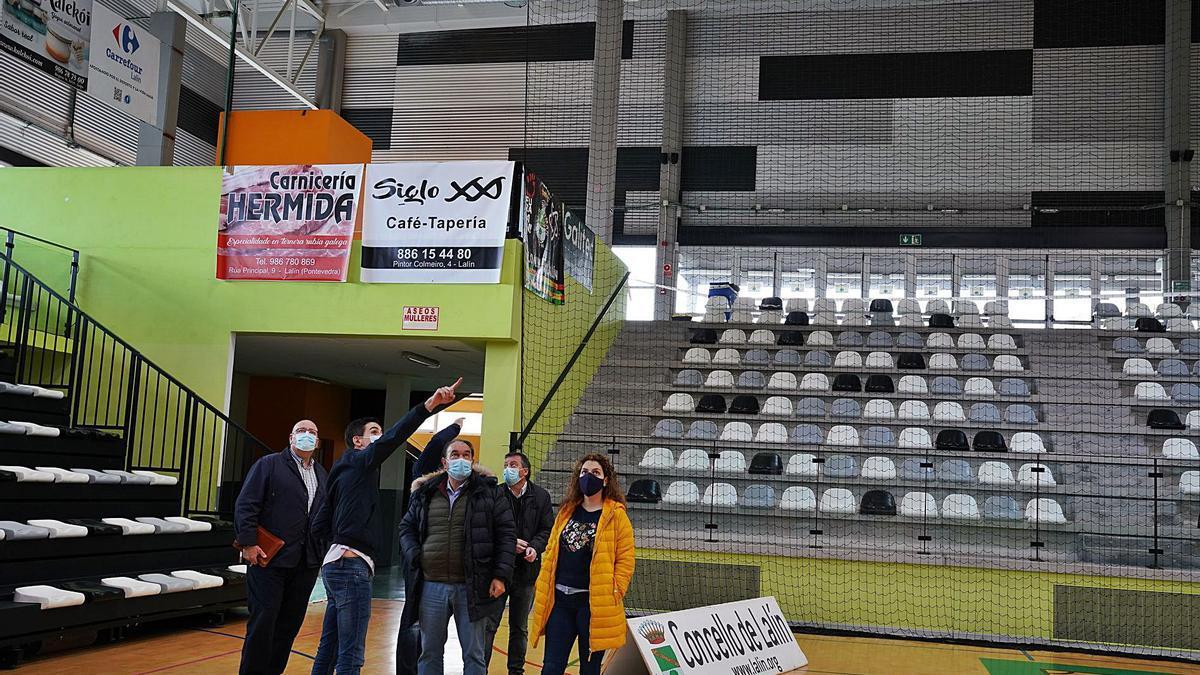 El edil de Deporte, Avelino Souto, señala hacia la lona del Lalín Arena, junto a políticos y miembros de Framiñán y Danosa.