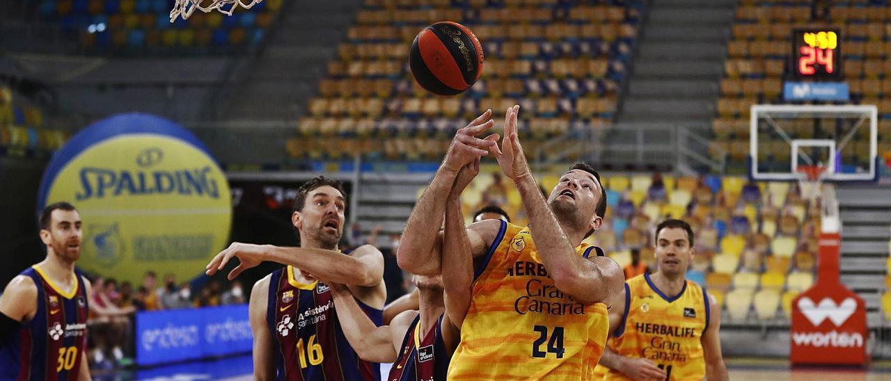 Matt Costello -24- lucha por un rebote con Pau Gasol -16- en el choque de ayer entre el Granca y el Barça. | | CBGC