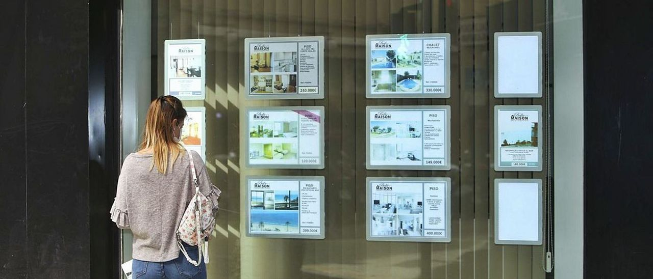 Una posible clienta observa las ofertas de una inmobiliaria en Alicante.