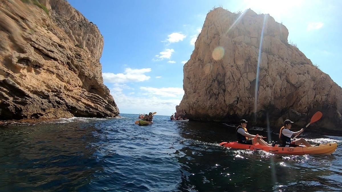 Participantes en una excursión de Xàbia Activa pasan en kayak entre el acantilado y un islote