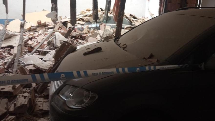 Dos coches destrozados tras desprenderse una terraza sobre un garaje en Moreda