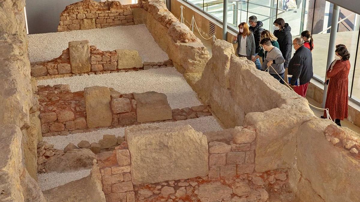 La alcaldesa y los arqueólogos, durante la visita a la Muralla; abajo, detalle de los objetos encontrados.  a.c.