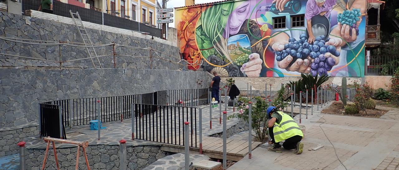 Un obrero trabaja en la terraza de la Casa del Vino de Santa Brígida donde se ve el grafiti de Matías Mata.