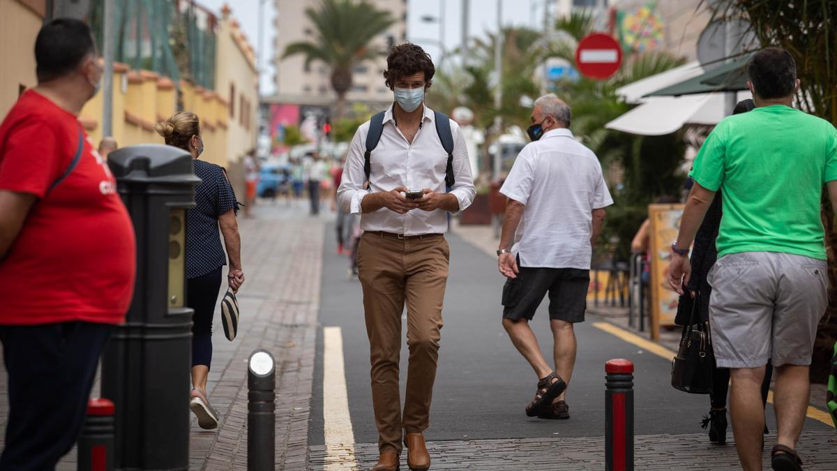 Un joven pasea con mascarilla por el centro de Santa Cruz de Tenerife.