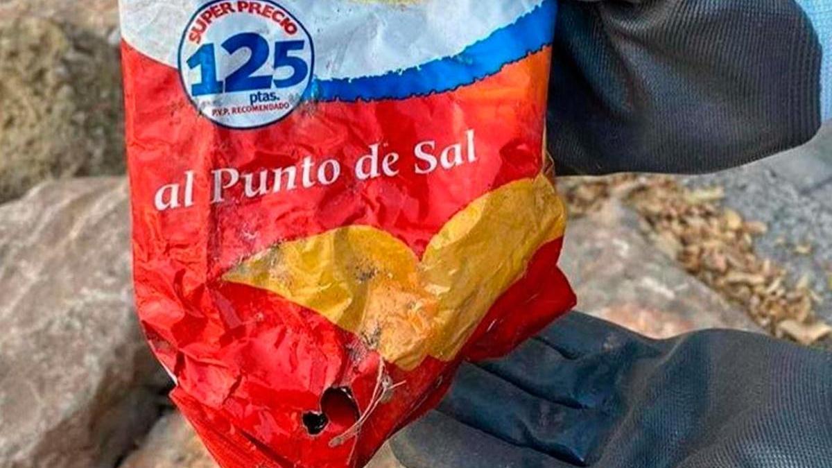 La bolsa de patatas fritas hallada entre las rocas de la playa alicantina del Postiguet tiene como mínimo 22 años.