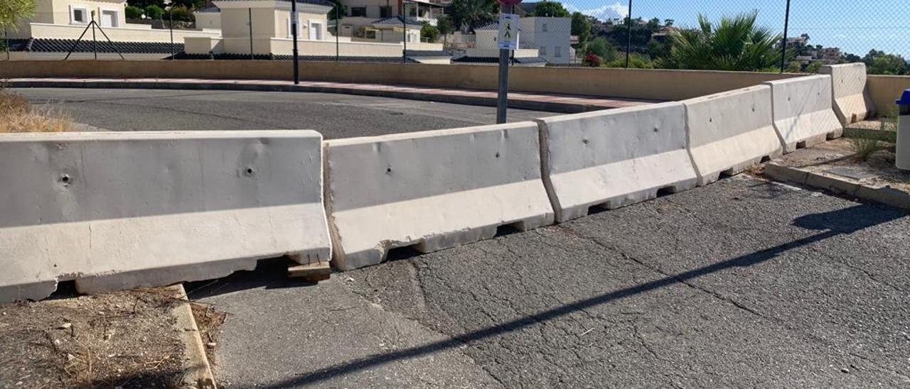Las vallas que cortaban la calle han sido sustituidas por bloques de hormigón. El muro inestable está situado a la derecha.
