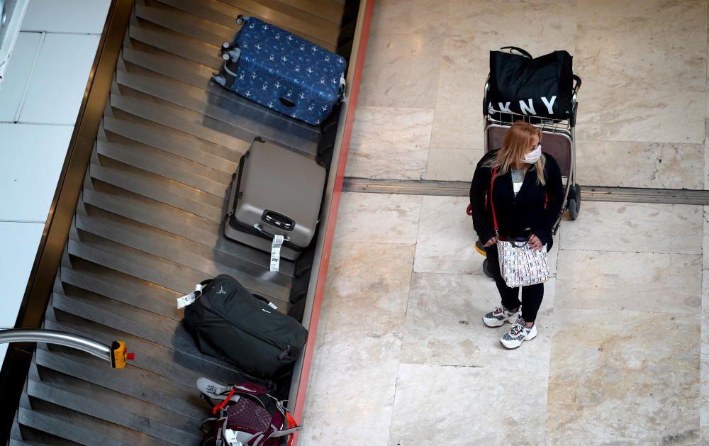 MADRID. 19.03.2020. CORONAVIRUS. Miembros de la UME limpian el aeropuerto de Barajas, terminal T4. En la imagen una mujer espera su maleta. FOTO: JOSE LUIS ROCA