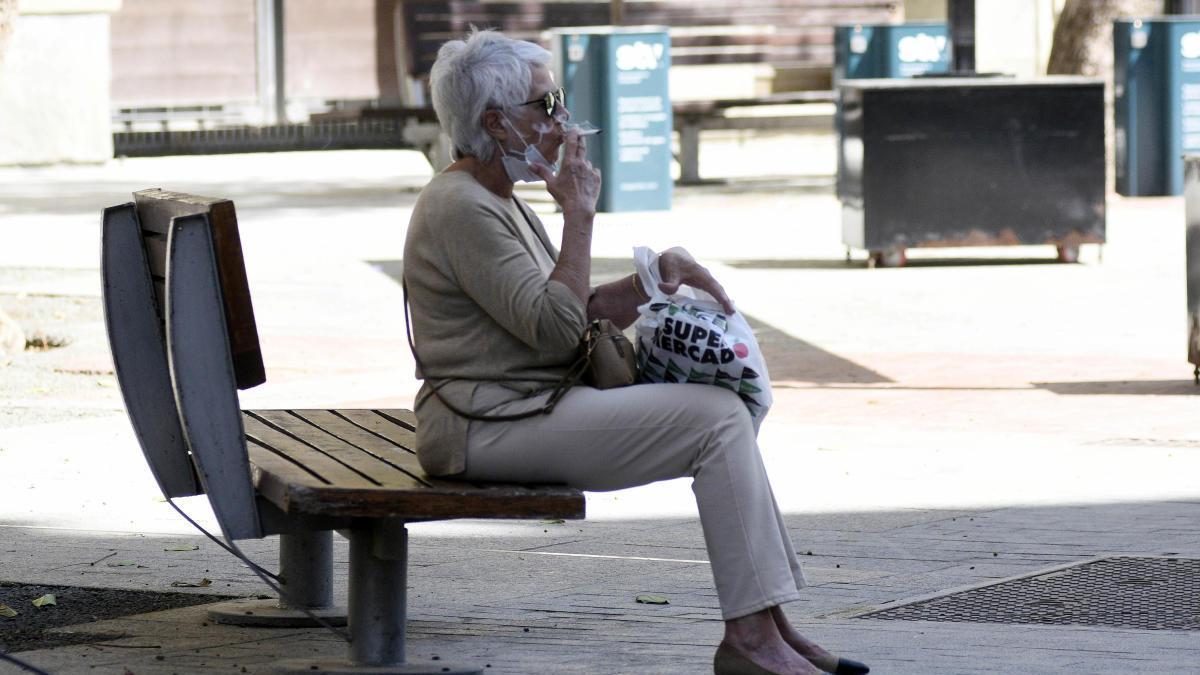 Una mujer con la mascarilla bajada fuma en un banco de la capital murciana, ayer. israel sánchez
