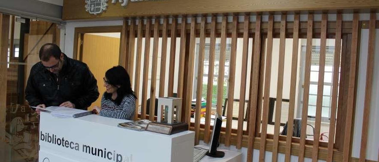 Sobre estas líneas, el aparejador municipal Juan José Pérez y Ana Méndez, en el renovado vestíbulo de entrada, junto a la oficina de trabajo de la biblioteca. A la derecha, Aitana Pérez, en la puerta de acceso a las nuevas instalaciones del telecentro.