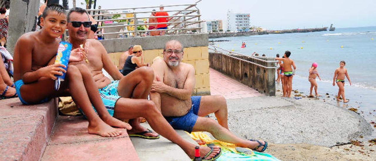 Antonio Morales, con su hijo en la playa de Arinaga.