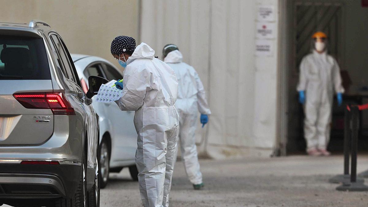 Varios sanitarios toman muestras para hacer PCR a coches en la carpa del Hospital General de València. | J. M. LÓPEZ