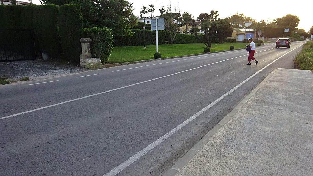 Una vecina cruza por la carretera del Portitxol de Xàbia | CARLOS LÓPEZ
