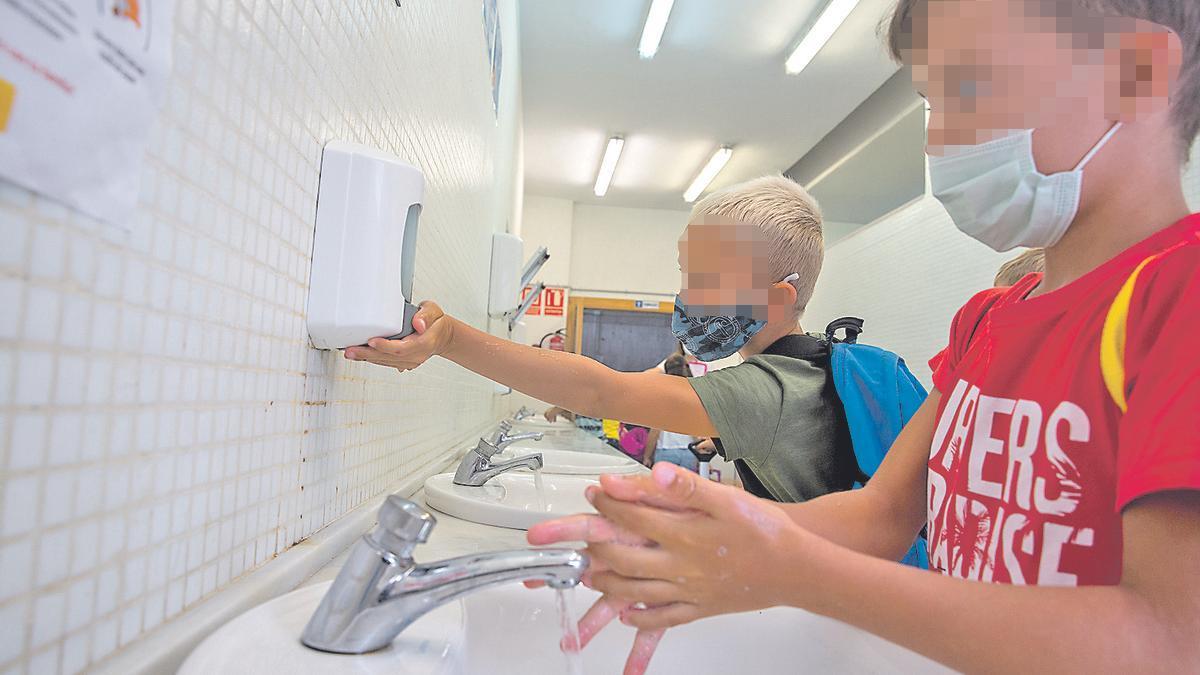Dos niños se lavan las manos  el primer día de colegio en  un colegio alicantino.