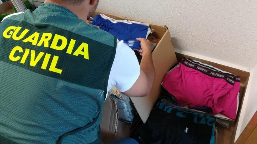Un agente revisa las prendas de ropa incautadas en el mercadillo de Toro.