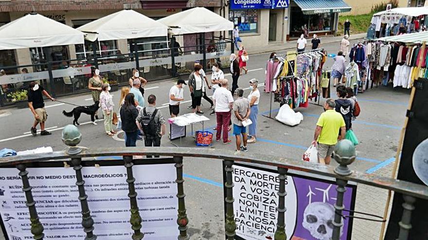 Vecinos recogen unas 150 firmas contra el parque eólico das Encrobas en un puesto en la feria de Carral