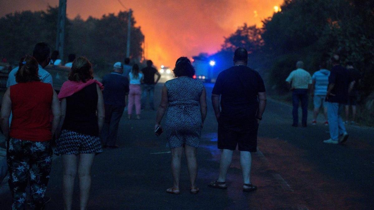 Vecinos de Cualedro (Ourense) observan el avance de el incendio forestal. // Brais Lorenzo (EFE)
