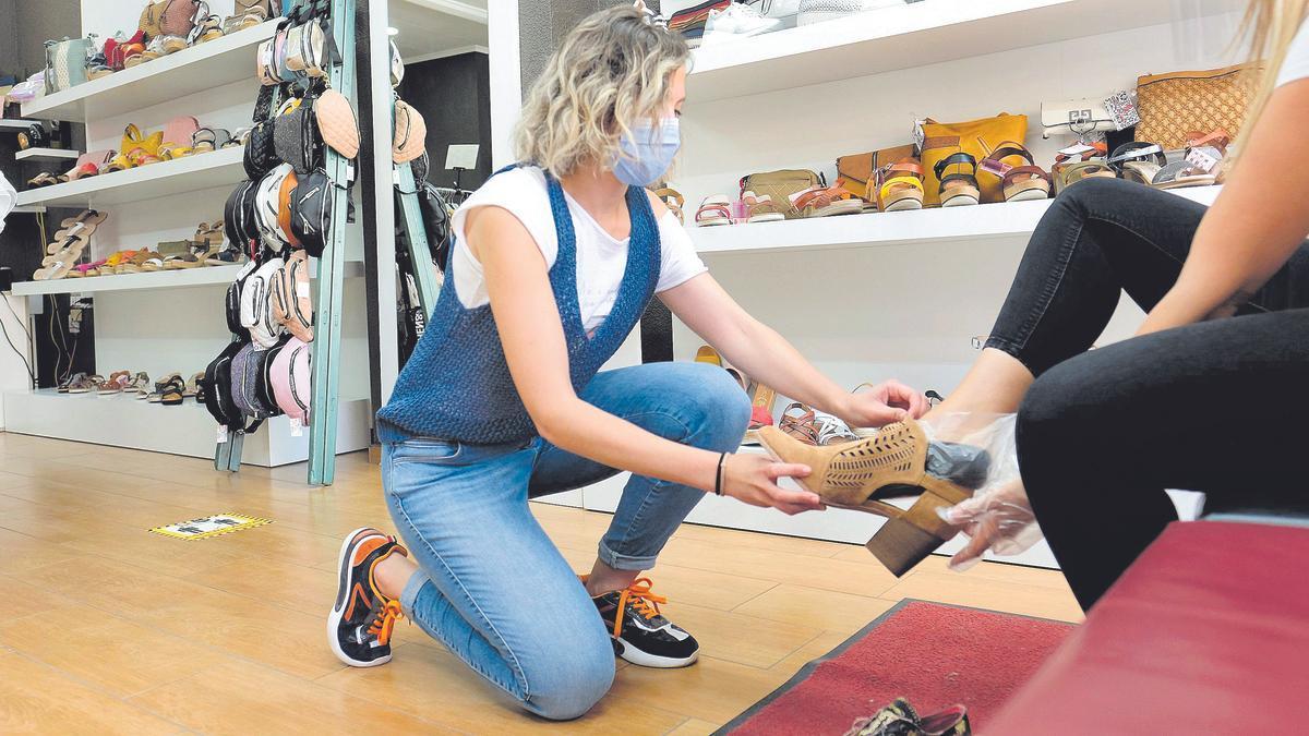 Una dependienta de un comercio ayuda a una clienta a probarse unos zapatos.