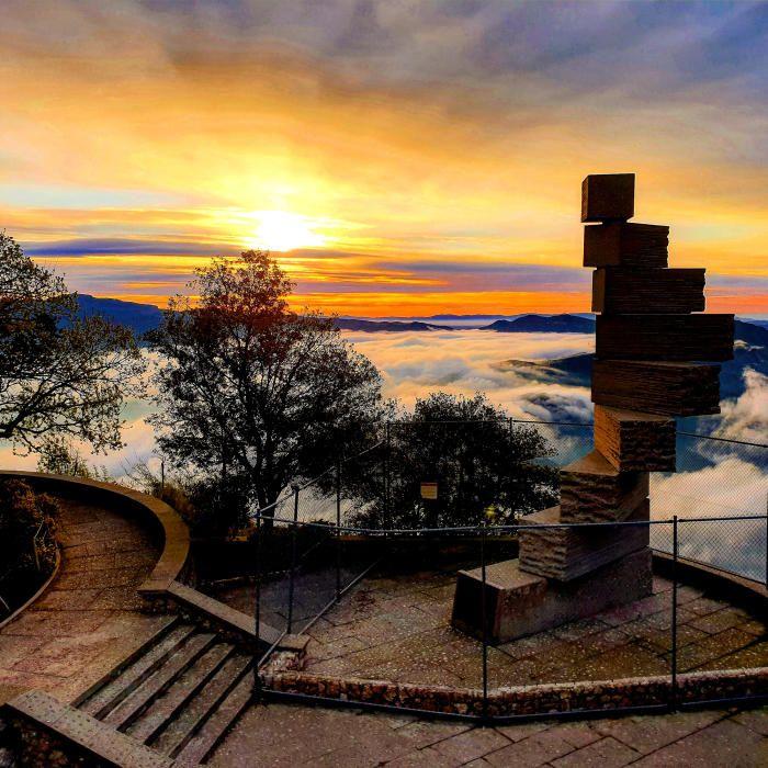 Montserrat. Tot i la catifa de núvols, els raigs de sol acoloreixen de color ataronjat el cel. En primer terme, a la dreta, l'escala de l'enteniment, al mirador dels Apòstols de Montserrat.