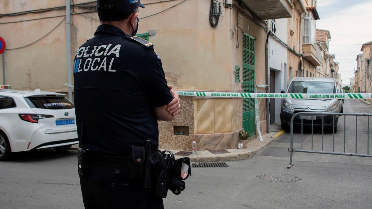 Un agente de la policía local vigila la casa donde se produjo el asesinato de una mujer embarazada y su hijo de 7 años