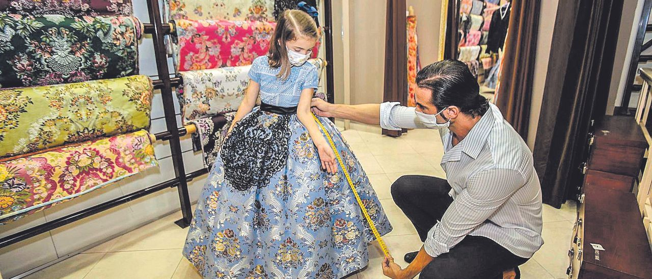 Una pequeña festera, ajustándose la falda en el taller del indumentarista Rubén Hernández.
