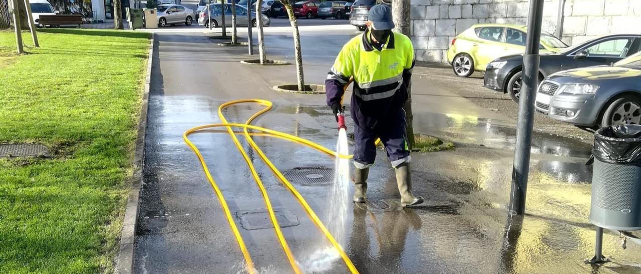 Un operario del servicio de limpieza viaria, realizando un baldeo en las inmediaciones de la Biblioteca Pública Municipal Antón de la Braña.   S. Arias