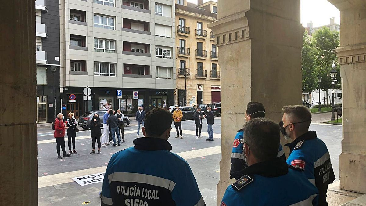 Agentes de Policía, de espaldas, ayer, en los soportales del Ayuntamiento. En la plaza, al fondo, los manifestantes.