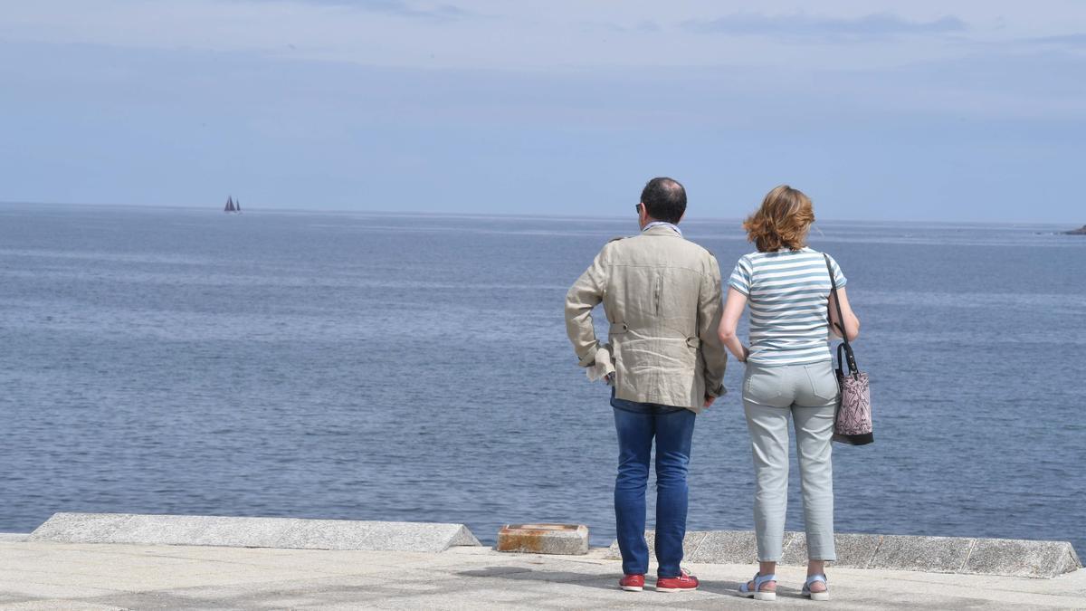 Dos personas observan el mar desde el paseo marítimo coruñés.