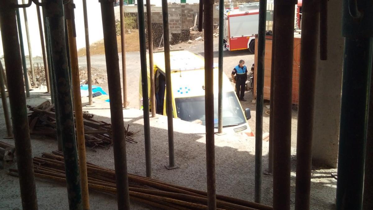 Un policía local de Tías junto entre la ambulancia y el vehículo de bomberos trasladado a la obra en la que se precipitó el obrero en Tías.